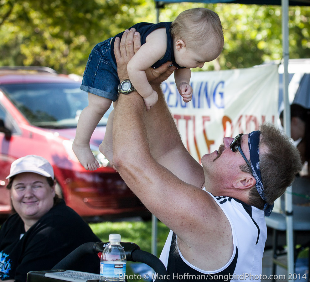 Burly dad and wee infant having fun at a corporate picnic for Zetron Corporation in Redmond, Washington.